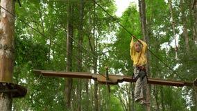Il ragazzino in un cavo di sicurezza scala su un itinerario in cime d'albero in un parco di avventura della foresta Scala sull'al archivi video