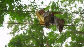 Il ragazzino in un cavo di sicurezza scala su un itinerario in un parco di avventura della foresta Scala sull'alta traccia della  stock footage