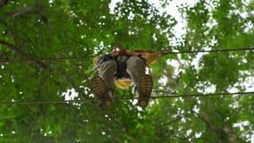 Il ragazzino in un cavo di sicurezza scala su un itinerario in un parco di avventura della foresta Scala sull'alta traccia della  archivi video