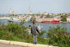 Il ragazzino in un rivestimento sta contro lo sfondo di un porto marittimo Fotografie Stock Libere da Diritti