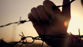 Il ragazzo è al tramonto dietro filo spinato Mani che tengono il cavo Concetto di immigrazione Siluetta di un bambino dietro la a stock footage