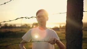Il ragazzo è al tramonto dietro filo spinato Mani che tengono il cavo Concetto di immigrazione Siluetta di un bambino dietro la a archivi video