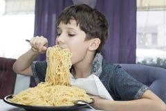 Il ragazzo è appetitoso mangia i grandi spaghetti italiani fotografia stock libera da diritti