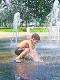 Il ragazzo è bagnato nella fontana fotografie stock libere da diritti