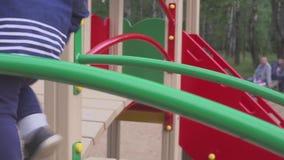 Il ragazzo è giocato su un campo da giuoco in un parco o in un asilo Il bambino è divertimento da giocare rumorosamente video d archivio