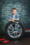 Il ragazzo è impegnato nella riparazione delle automobili delle ruote Fotografia Stock Libera da Diritti