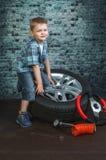 Il ragazzo è impegnato nella riparazione delle automobili delle ruote Immagine Stock