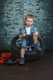 Il ragazzo è impegnato nella riparazione delle automobili delle ruote Fotografie Stock Libere da Diritti