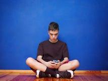 Il ragazzo è letto su uno smartphone Vicino alla parete immagini stock