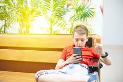 Il ragazzo è serio con uno smartphone e l'orologio astuto sta sedendosi sul banco e sta esaminando il telefono Foto con la tintur immagine stock