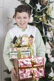 Il ragazzo è sopraffatto con molti regali di Natale Fotografie Stock