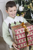 Il ragazzo è sorpreso con un grande regalo di Natale Fotografie Stock