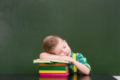 Il ragazzo addormentato su un mucchio dei libri si avvicina alla lavagna vuota Fotografia Stock