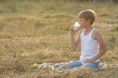 Il ragazzo adolescente dell'agricoltore con gli occhi chiusi beve il latte Fotografie Stock Libere da Diritti
