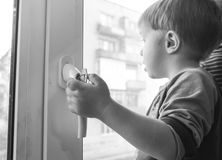 Il ragazzo afferra la maniglia della finestra Un piccolo bambino che tiene t Immagini Stock Libere da Diritti
