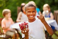 Il ragazzo africano mangia le ciliege Fotografia Stock Libera da Diritti