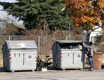 Il ragazzo africano povero sta provando alcuni vestiti nella scatola residua Fotografie Stock