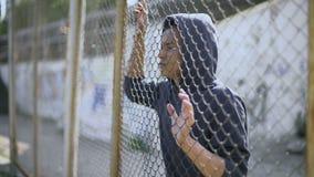 Il ragazzo afroamericano dietro il recinto, bambino emigrante ha separato dalla famiglia, detenuta stock footage