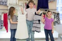 Il ragazzo aiuta le ragazze sveglie a scegliere il vestito in negozio Fotografie Stock