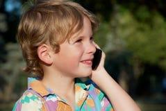 Il ragazzo allegro con un telefono mobile Immagini Stock Libere da Diritti