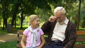 Il ragazzo allegro dice lo scherzo al nonno, ridendo insieme, divertendosi all'aperto archivi video