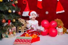 Il ragazzo allegro disimballa i regali di Natale a casa immagini stock libere da diritti