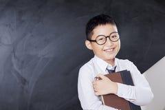Il ragazzo allegro tiene il libro in aula Immagine Stock