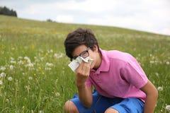 Il ragazzo allergico con i vetri soffia il suo naso Fotografia Stock Libera da Diritti