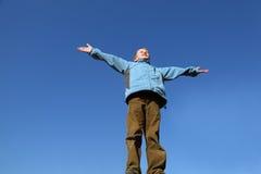 Il ragazzo alza le sue braccia a cielo blu Fotografia Stock