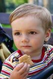 Il ragazzo ambulante mangia i biscotti Fotografia Stock Libera da Diritti