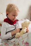 Il ragazzo ammalato sta giocando con uno stetoscopio Immagine Stock