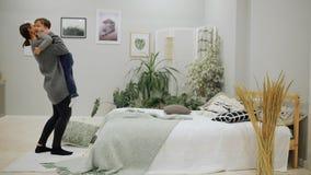 Il ragazzo 5-7 anni in blue jeans ed in un aspetto europeo del maglione grigio che salta felicemente sul letto si avvicina mamma  archivi video