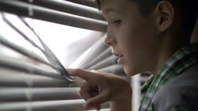 Il ragazzo apre i ciechi e guarda fuori la finestra con la sorpresa fotografia stock libera da diritti