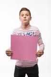 Il ragazzo artistico castana in un saltatore rosa con un foglio di carta rosa per le note Immagini Stock Libere da Diritti