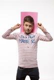Il ragazzo artistico dell'adolescente castana in un saltatore rosa con un foglio di carta rosa per le note Immagini Stock Libere da Diritti