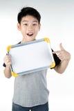 Il ragazzo asiatico è poco sorriso con la camma in bianco di sguardo e del bordo bianco Fotografia Stock Libera da Diritti