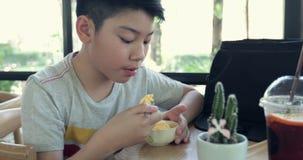 Il ragazzo asiatico felice gode di di mangiare il gelato stock footage