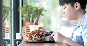 Il ragazzo asiatico gode di di mangiare la frutta della miscela con la cialda stock footage