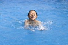 Il ragazzo asiatico sta nuotando nel raggruppamento immagini stock libere da diritti
