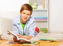 Il ragazzo astuto con il libro ed il manuale mettono sul pavimento Fotografie Stock Libere da Diritti