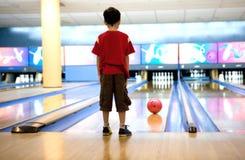 Il ragazzo attende pazientemente mentre la sua sfera di bowling rotola Immagine Stock