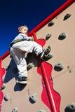 Il ragazzo attivo arrampica una parete Immagini Stock Libere da Diritti