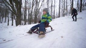 Il ragazzo attivo del bambino guida sulla slitta da una montagna nevosa nella foresta, festa della famiglia stock footage