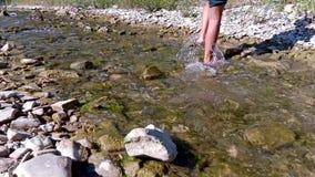 Il ragazzo attraversa la corrente piedi di primo piano del ragazzo su un fondo della corrente e delle rocce della foresta Il conc stock footage
