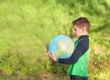 Il ragazzo bello sta tenendo un globo Allievo nel parco, studiare Immagine Stock