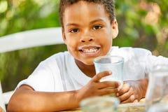 Il ragazzo beve un bicchiere di latte sano fotografia stock libera da diritti
