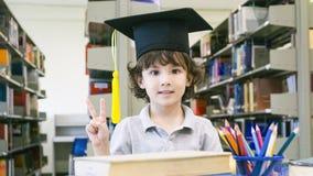 Il ragazzo bianco sorridente con la carta del cappuccio e del diploma di graduazione sta Fotografie Stock