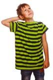 Il ragazzo biondo in camicia verde a strisce pensa lo scratch fotografia stock