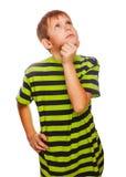 Il ragazzo biondo del bambino in maglietta verde pensa lo scratch Fotografia Stock
