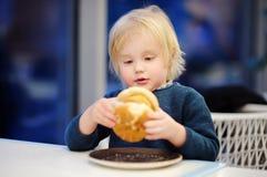 Il ragazzo biondo sveglio mangia l'hamburger al fast food Immagini Stock